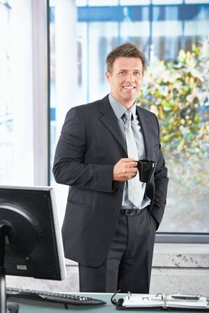 Happy confident businessman in suit standing by office desk smiling holding cofee mug. photo
