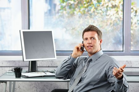 Gesturing businessman speaking on mobile phone sitting in sunlit office. Stock Photo - 6338845