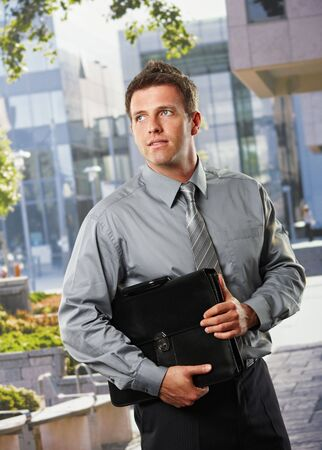 Smiling businessman holding briefcase standing outside office building in sunshine. photo