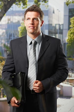 Smart executive in suit standing on office building courtyard holding briefcase. photo