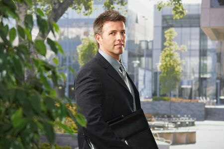 Portrait of mid-adult executive businessman standing in front of office building with briefcase looking at camera smiling. photo
