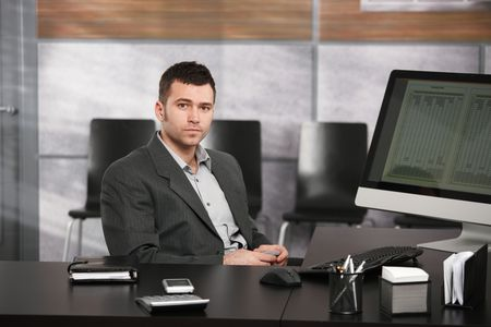 unsmiling: Portrait of young businessman sitting at office desk, holding mobile phone, looking at camera. Stock Photo
