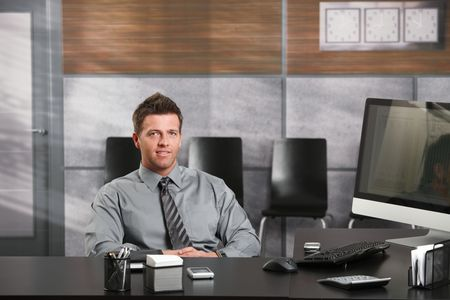 Portrait of happy businessman sitting at office desk, looking at camera, smiling. photo