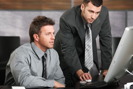 Two businessmen working together with computer at office desk, looking at screen. photo
