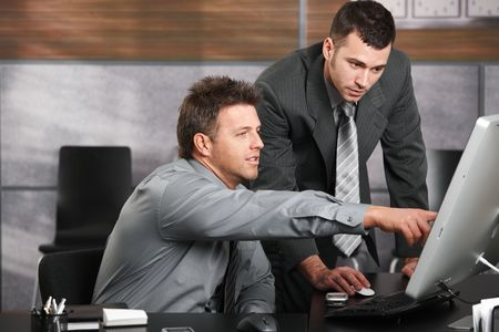 Two businessmen working together with computer at office desk, one of them pointing at screen. photo