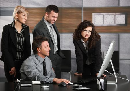 Happy business people working in office, looking at computer screen talking smiling. photo