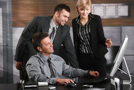 Businessman sitting at office desk, looking at screen together with colleagues, smiling. photo