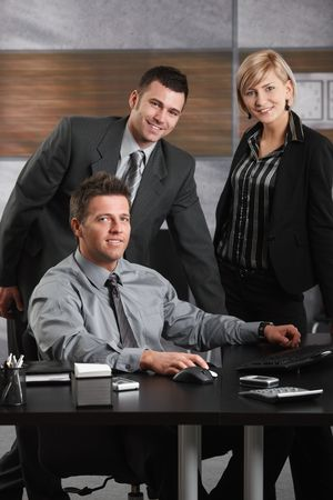 Portrait of happy businessman and team at office desk, looking at camera, smiling. photo