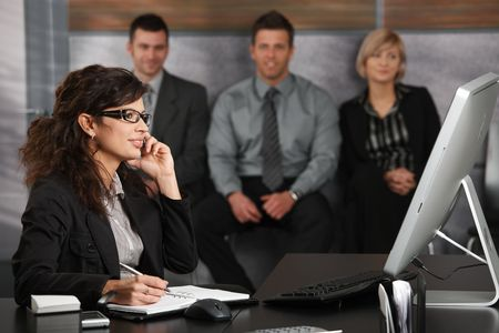 Young businesswoman sitting at desk in office recepcion, talking on mobile phone, smiling, people waiting in background. photo