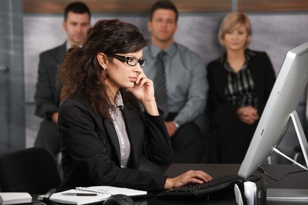 businessman waiting call: Young receptionist sitting at desk in office recepcion, talking on mobile phone, smiling, people waiting in background.
