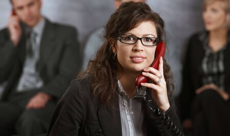 Closeup portrait of young businesswoman talking on landline phone, smiling. photo