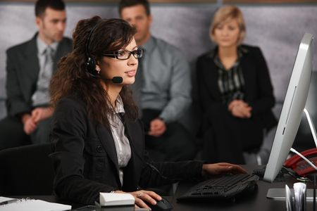 Receptionist sitting at desk in office, talking on headset, using desktop computer, smiling. photo