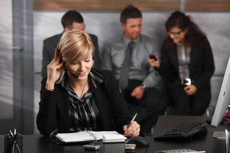 Young businesswoman sitting at desk in office, talking on headset, looking at personal organizer, smiling. photo