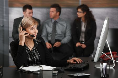 Young receptionist sitting at desk in office recepcion, talking on mobile phone, smiling, people waiting in background. photo