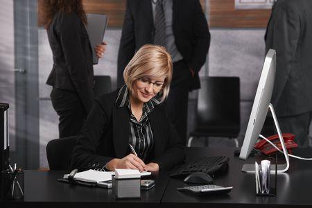 mujer con corbata: Joven empresaria sentado en el escritorio de la Oficina, tomando notas, sonriendo. Foto de archivo