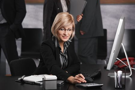 Young businesswoman sitting at office desk, using calculator, smiling. photo