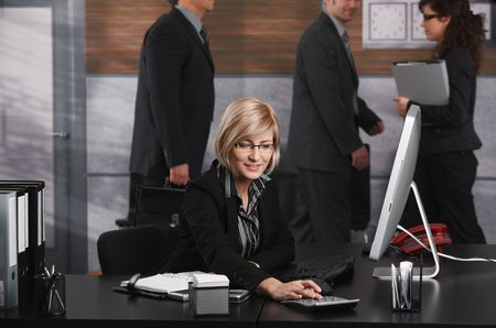 Young blond businesswoman sitting at office desk, using calculator, smiling. photo