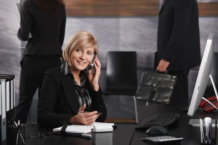 Happy young businesswoman sitting at office desk talking on mobile phone, smiling. photo