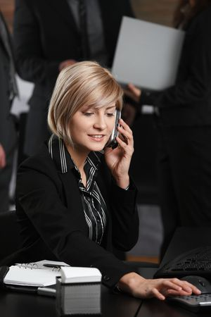 Happy young businesswoman sitting at office desk talking on mobile phone, using calculator, smiling. photo