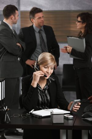 Young businesswoman sitting at desk in office, talking on headset, using PDA, smiling. photo