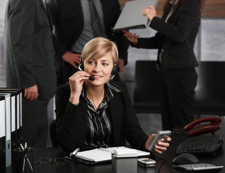 Young businesswoman sitting at desk in office, talking on headset, smiling. photo