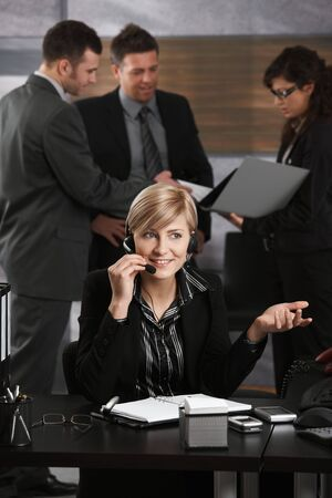 Happy young receptionist receiving phone calls on headset in office smiling. photo