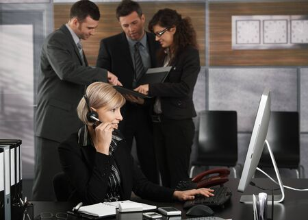 Happy young receptionist talking on headset in office smiling. photo