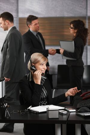 Young businesswoman sitting at desk in corporate office, talking on headset, smiling. photo