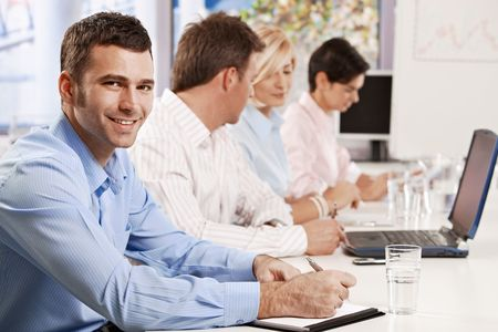 Young businessman making notes on business presentation at office, looking at camera, smiling. Stock Photo - 6373654