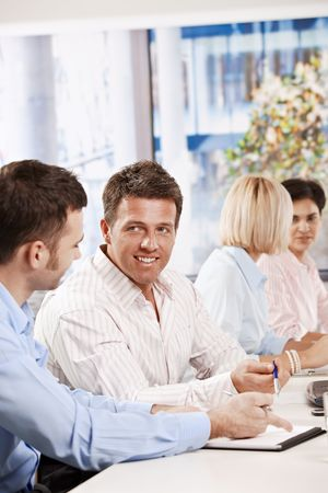 Happy business people talking on meeting at office smiling. photo