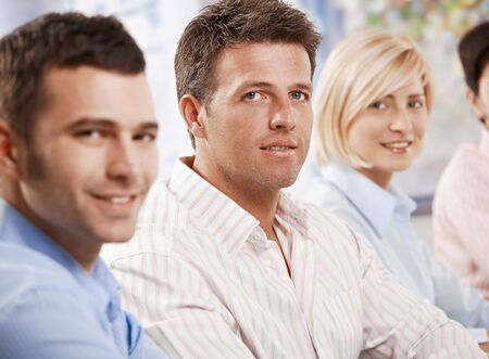 Businessman sitting in meeting with coworkers, looking at camera, smiling. Stock Photo - 6373751