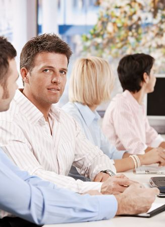 Businessman sitting at desk having meeting in office, looking at camera, smiling. photo