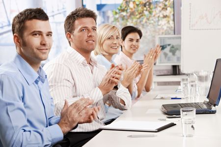 Happy business people sitting at table in meeting room clapping listening to presentation. photo