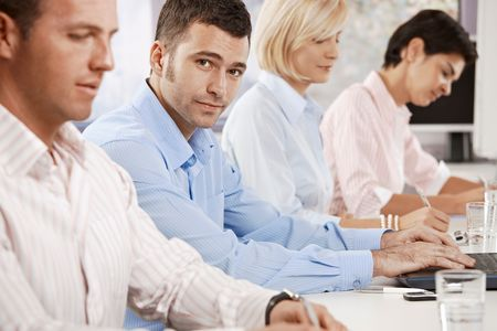 Mid-adult businessman sitting on business meeting with colleagues at office, looking at camera. photo