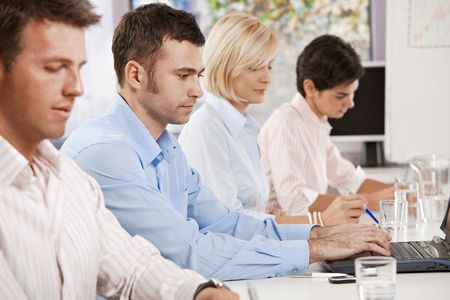 Young businessman sitting on business meeting with colleagues at office. photo