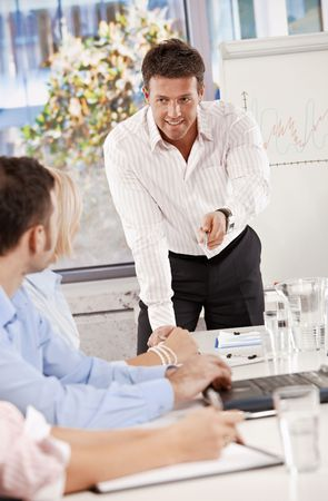 Businessman doing business presentation in meeting room, smiling. Stock Photo - 6373645
