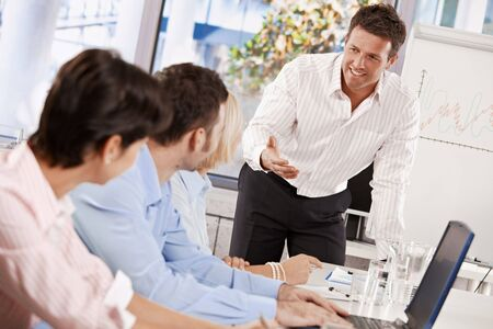 doing business: Businessman conducting business presentation in meeting room, talking smiling.
