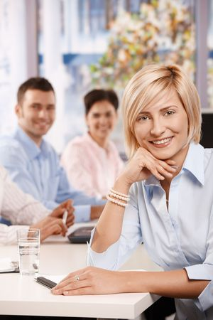 good looking woman: Happy businesswoman on business meeting at office, leaning on table, looking at camera and smiling.