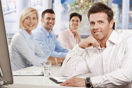 Happy businessman sitting at table in meeting room at office, looking at camera smiling photo