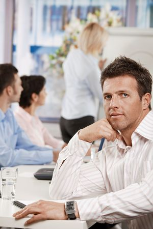 Businessman sitting at table in meeting room at office, looking at camera. photo
