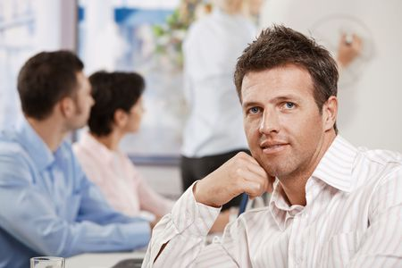 Satisfied mid-adult businessman in business meeting at office, looking at camera smiling. Stock Photo - 6373766