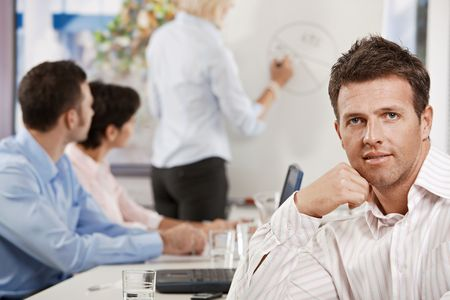 Satisfied mid-adult businessman in business meeting at office, looking at camera smiling. photo