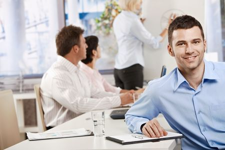 Happy young businessman in business meeting at office, looking at camera smiling. photo