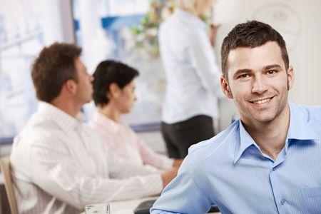 Heureux jeune entrepreneur en séance de travail au bureau, regardant le sourire de la caméra.