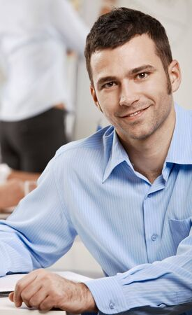 Happy businessman sitting at table in meeting room, looking at camera, smiling. photo