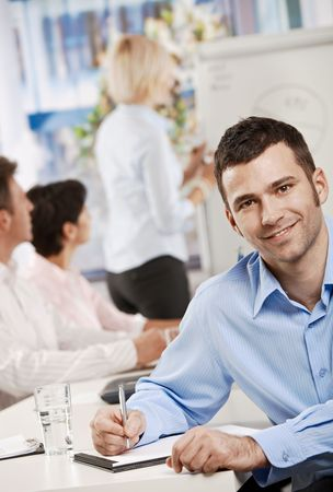 Happy businessman sitting at table in office writing notes on business meeting, looking at camera, smiling. photo