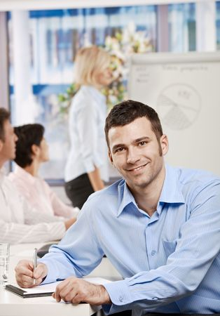 Happy businessman sitting at table in office writing notes on business meeting, looking at camera, smiling. Stock Photo - 6373720