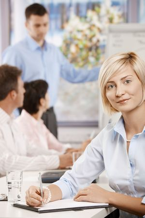 Young businesswoman sitting on business meeting in office making notes, looking at camera smiling. Stock Photo - 6373688
