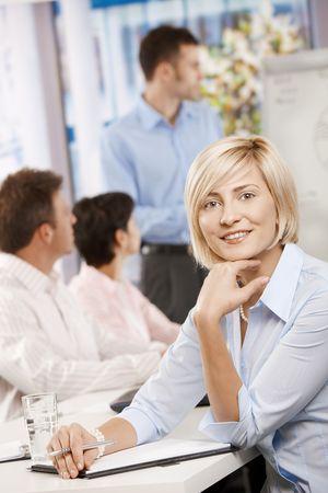 formacion empresarial: Feliz empresaria sentado en la reuni�n de negocios en la Oficina haciendo notas, mirando a la c�mara sonriendo.