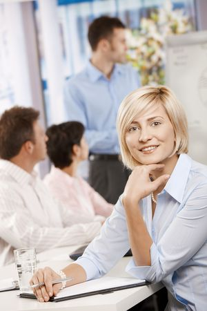 Happy businesswoman sitting on business meeting in office making notes, looking at camera smiling. Stock Photo - 6373625